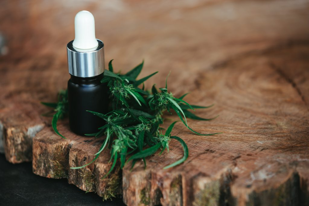 Un flacon d'extrait d'huile CBD posé sur une table en bois